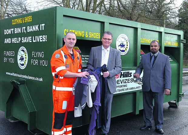 This Is Wiltshire: Pictured at Hills' Compton Bassett Air Ambulance textiles bin is, from left, paramedic Matt Baskerville, Steve Burns, divisional director for Hills Waste Solutions, and Shahid Siddiq, director of Devizes Textiles