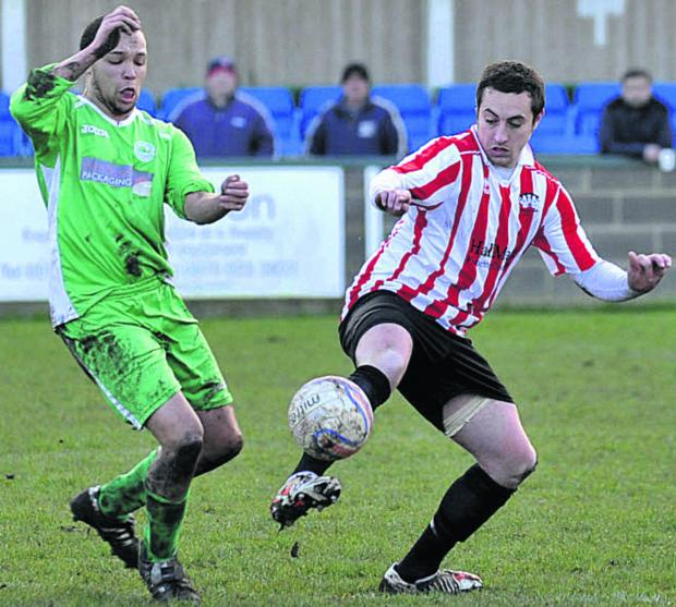This Is Wiltshire: Devizes Town's Robbie Mitchell battles with Westbury's Dan Hurkett in last weekend's clash