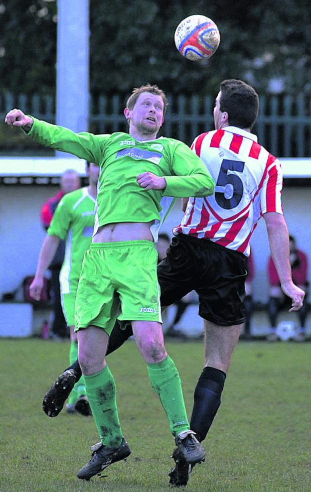This Is Wiltshire: Westbury's Marc Lanfear (green) battles in the air with Devizes' Gareth Davies