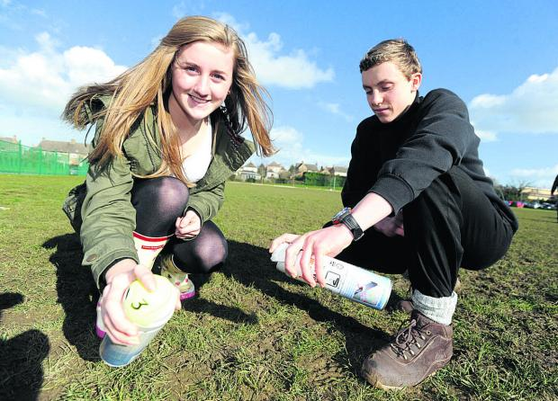 This Is Wiltshire: Year 10 students Jenna and Ollie get ready to spray a 'crop circle' design in the shape of a Dyson Airblade drier.        (DV1138) By diane vose