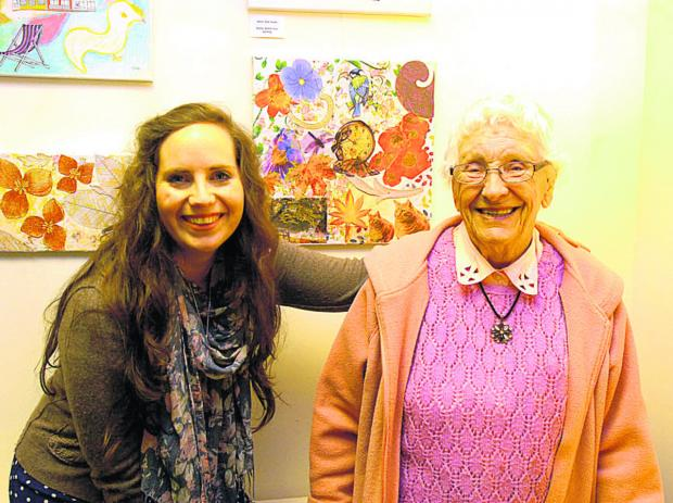This Is Wiltshire: Art teacher Emma Burbidge with 94-year-old Vera Wardell and some of the artwork, which is on display at Pewsey Gallery this month