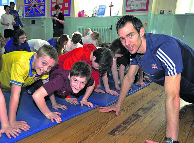 This Is Wiltshire: Commonwealth athlete Robert Mitchell leading a fitness session with pupils at Churchfields School, Atworth