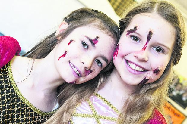 This Is Wiltshire: Keira, left, and Charlotte in all their gory glory as Tudors with the bubonic plague, from one of the the Horrible Histories books