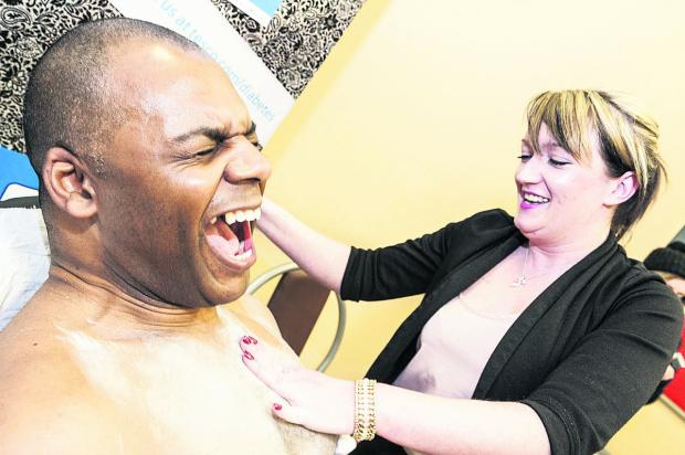 This Is Wiltshire: Leroy Robinson,  the manager of Tesco in  Ocotal Way, getting his chest waxed by Samantha McHugh as part of the store's fundraising for Diabetes UK