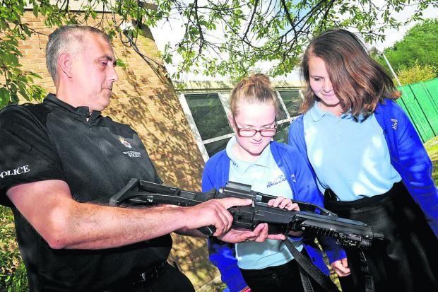 This Is Wiltshire: PC Shaun Dodson shows Dorcan Academy pupils Emily Miles and Lauren Rogers a firearm in a bid to make pupils aware of the dangers and, below, swords seized during the Operation Harness day of action in January