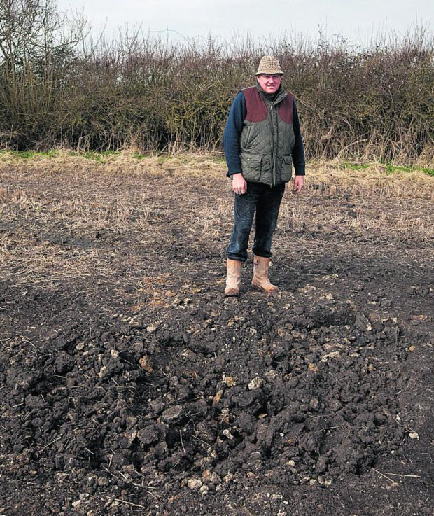 This Is Wiltshire: Andrew Snook next to the crater on his farm at Patney. An Army shell l