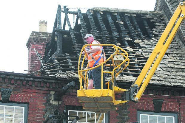 This Is Wiltshire: Inspecting the charred remains of the Cross Key's roof following last July's devastating fire. The pub is now due to be repaired
