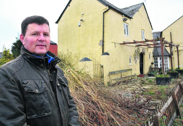 This Is Wiltshire: Bishopstone councillor Ian Thomas at the former True Heart pub. Plans have been submitted to restore it and build new houses on the site