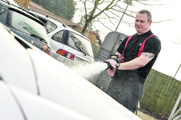 This Is Wiltshire: Fire Fighter Wayne Nelhans gives a car a good clean using a hosepipe