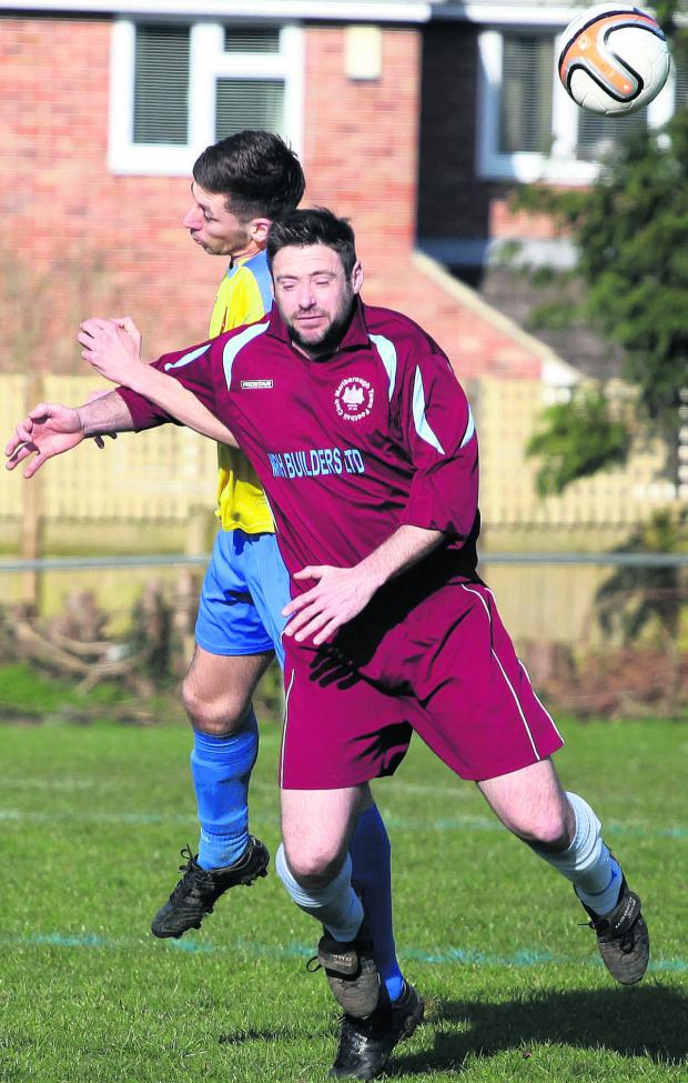 This Is Wiltshire: Marlborough Town's Leigh Blanchard (burgundy) challenges Corsham Town Reserves' Josh Batstone in the air during Saturday's Wiltshire League Premier Division clash