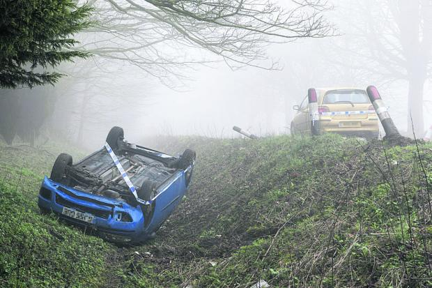 This Is Wiltshire: A Fiat Punto overturned on Brimble Hill, Wroughton, after the driver swerved to avoid a deer. Picture: ALEX SKENNERTON