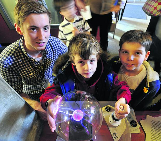 This Is Wiltshire: Bath University's Steffan Goold, left, shows George Lancaster and Alex Pyper how static electricity from a plasma sphere can light up a fluorescent bulb