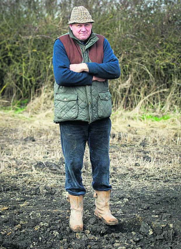 This Is Wiltshire: Andrew Snook next to the crater on his farm at Patney after an Army shell landed in a field near the main Penzance-Paddington railway line