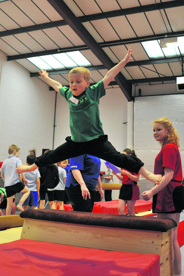 This Is Wiltshire: Matthew from St John's Primary School, top, takes a star leap over a box