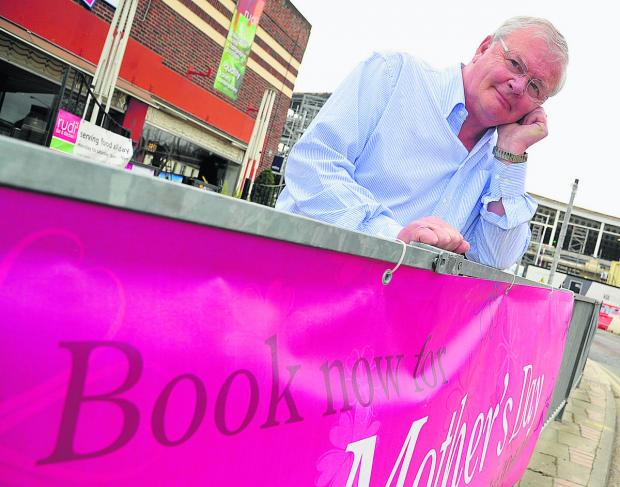 This Is Wiltshire: Paul Notton, owner of Rudi's Bar, with the banner advertising Mother's Day. Picture: DAVE COX