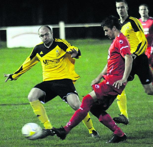 This Is Wiltshire: Melksham Town's Shaun Benison (yellow) challenges Jamie Richards, of Purton, in Tuesday night's Wiltshire Senior Cup semi-final