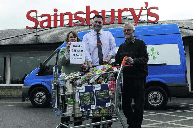 This Is Wiltshire: Tricia and Rob Munday each side of Sainsbury's store manager Darren Clare at Bradford on Avon. Shoppers donated 245kg of food stuffs for Bath Food Bank in ten weeks this spring