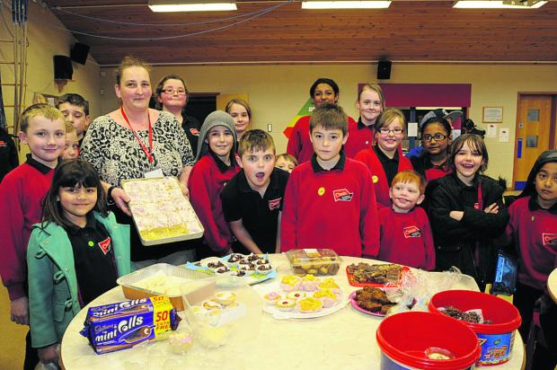This Is Wiltshire: Chairman of the friends Caroline Morris with cakes being snapped up by pupils at Oas