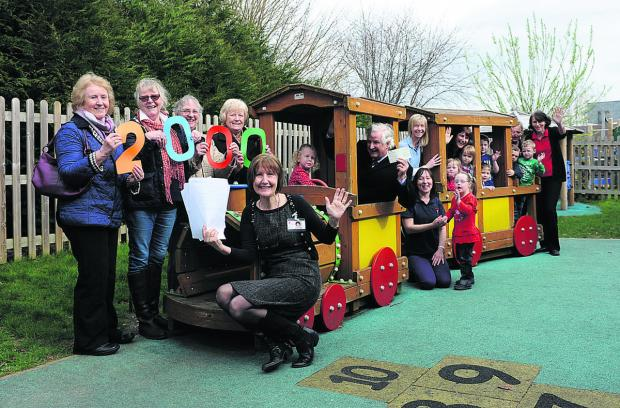 This Is Wiltshire: Westbury League of Friends representatives Sheila Stafford, Erica Watson, Kathryn Cundick, Shirley Baker and treasurer Peter Baker in the driving seat, with Stepping Stones manager Debbie Wickham, staff and pupils