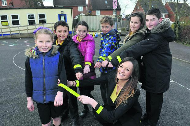 This Is Wiltshire: Taylor Wimpey sales and marketing co-ordinator Sarah-Jane Langton with the high-visibility slap bands the firm has donated to children at Wanborough Primary School