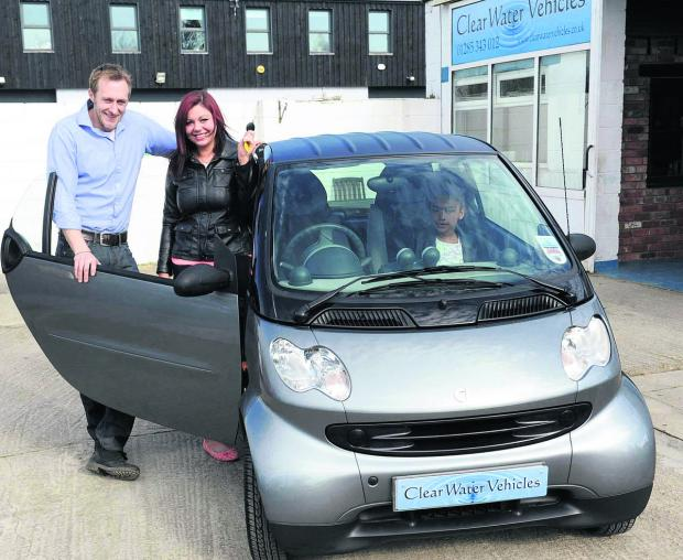 This Is Wiltshire: Richard King, from Clear Water Vehicles, hands over the keys to a Smart Car to Hayley Gooden as his Random Act Of Kindness