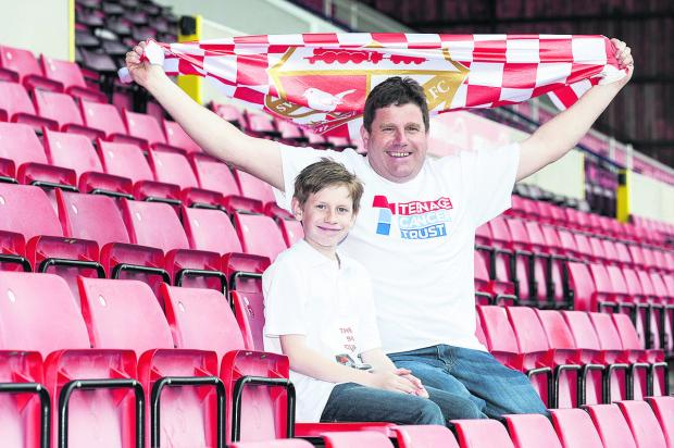 This Is Wiltshire: Darren Bungay and his son Richard at Swindon's County Ground as part of their plan to visit  92 football clubs to raise money for the Teenage Cancer Trust