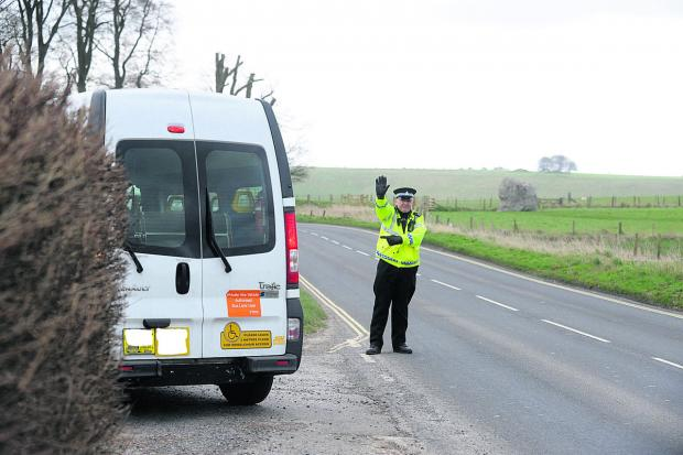 This Is Wiltshire: A police officer stops a van during the day of action