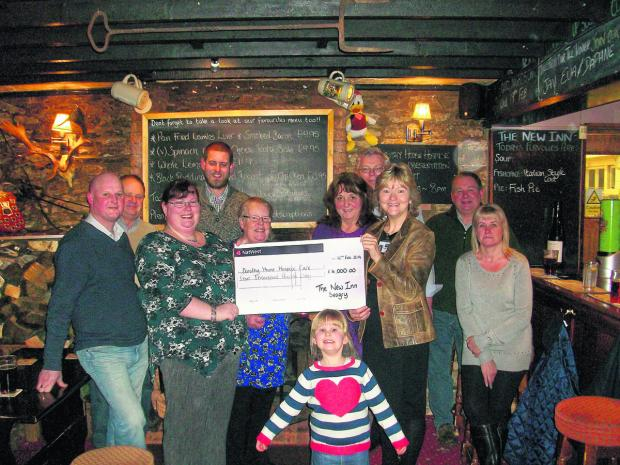 This Is Wiltshire: Upper Seagry fundraisers with their cheque for £4,000: Toddy Park, George Candy, Sarah and Karl Adkins, Helen Greenhill, Viv Read, John Greenhill, Yvonne Brunton  from Dorothy House, John Branston, Lorraine Drummond and, front, Grace Adkins