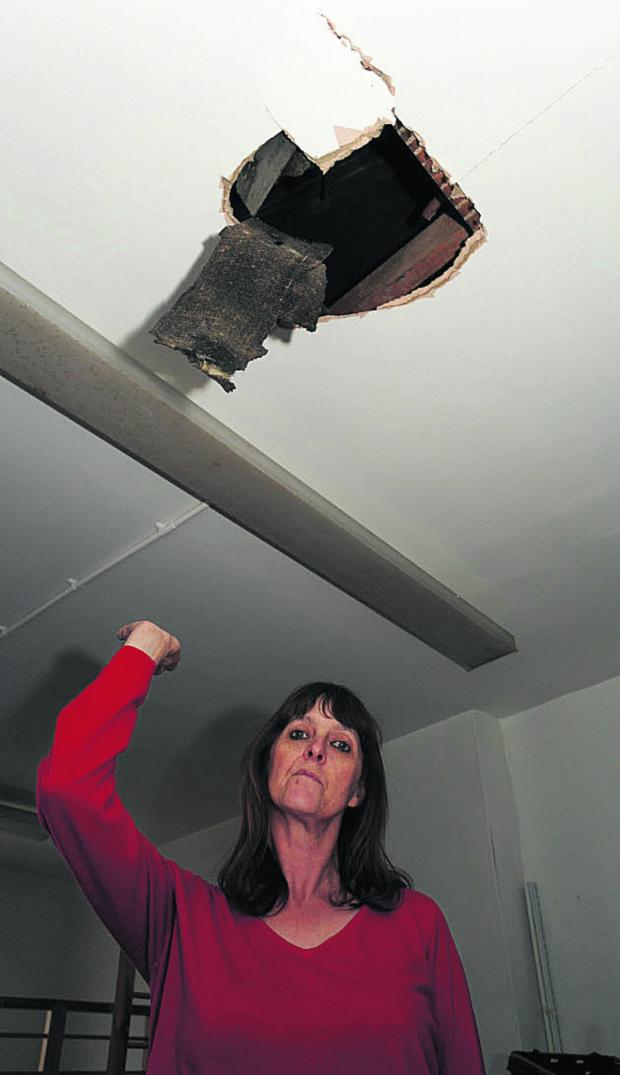 This Is Wiltshire: Age UK sales assistant Caroline Dutch shows some of the damage caused during the break-in