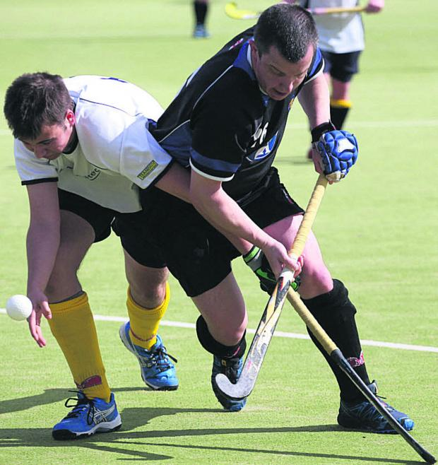 This Is Wiltshire: Devizes' Roger Edwards (black) battles with Team Bath Buccaneers 4th's Will Mainwaring during Saturday's 5-3 win, which wrapped up promotion