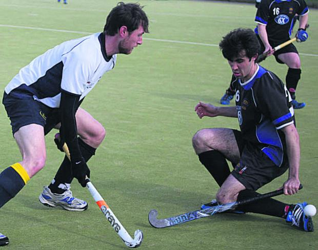 This Is Wiltshire: Devizes' Callum Lavens (right) tries to block the progress of Team Bath's Rich Warwick during his side's 6-1 victory on Saturday that wrapped up promotion from Davis Wood League Central One