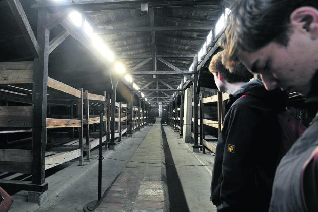 This Is Wiltshire: Youngsters survey primitive conditions in a hut at Birkenau