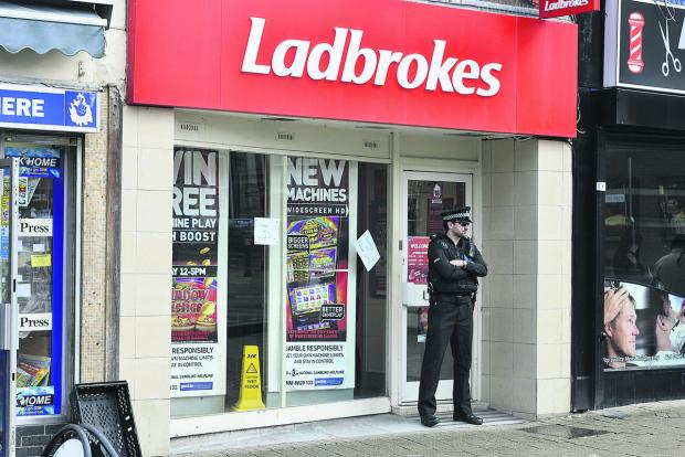 This Is Wiltshire: A police officer stands guard outside Ladbrokes in Regent Street. Picture: ALEX SKENNERTON