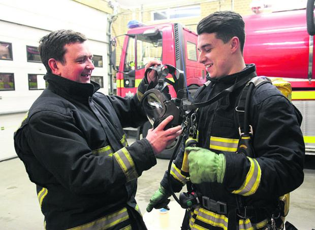 This Is Wiltshire: Firefighter Stuart Hillier shows Zac Messenger how to use breathing apparatus