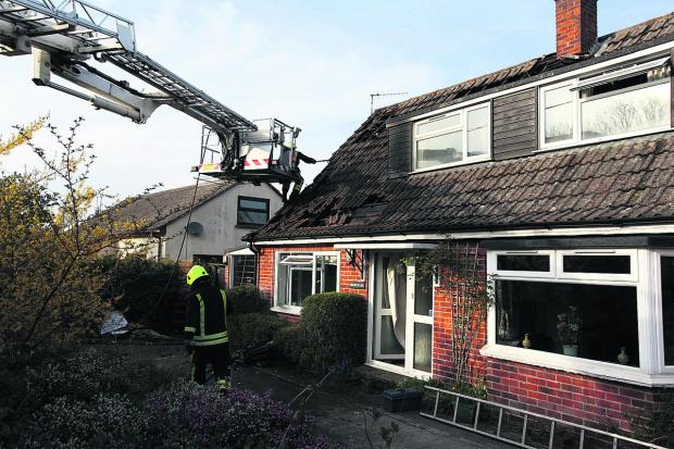 This Is Wiltshire: A firefighter on an aerial appliance gets in close to the seat of the blaze