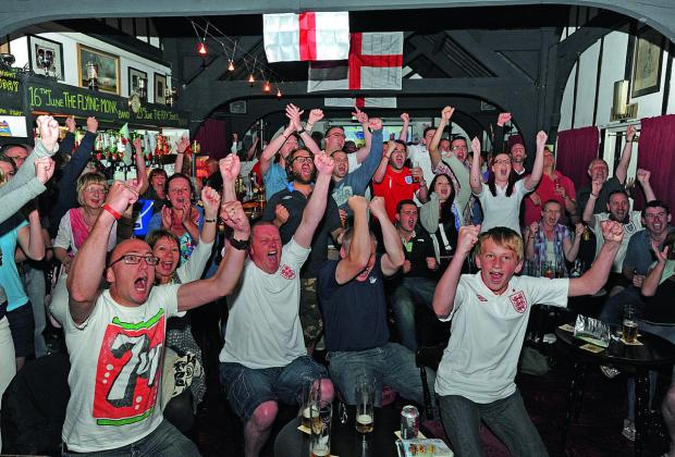 This Is Wiltshire: England fans celebrate a goal for the team in a packed pub