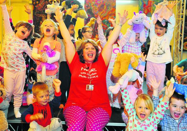 This Is Wiltshire: Lynn Hawkins helps an enthusiastic group of children break the sound barrier in one of the eight Make a Noise concerts at The Platform