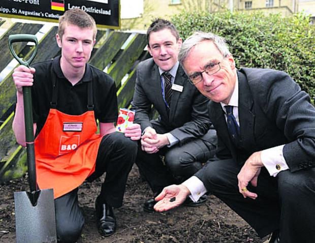 This Is Wiltshire: Chris Morrison, of B&Q, Nicholas Reid, Trowbridge Station manager, and Dr Andrew Murrison MP planting poppy seeds