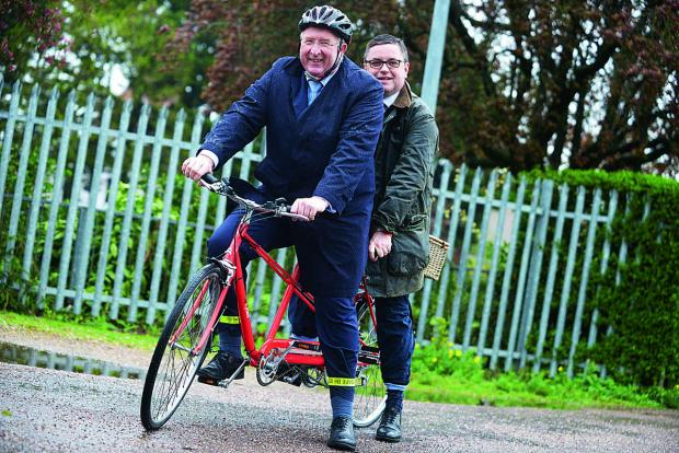 This Is Wiltshire: Angus Macpherson and MP Robert Buckland try out one of the tandem bikes for hire at the Salvation Army Recycles store
