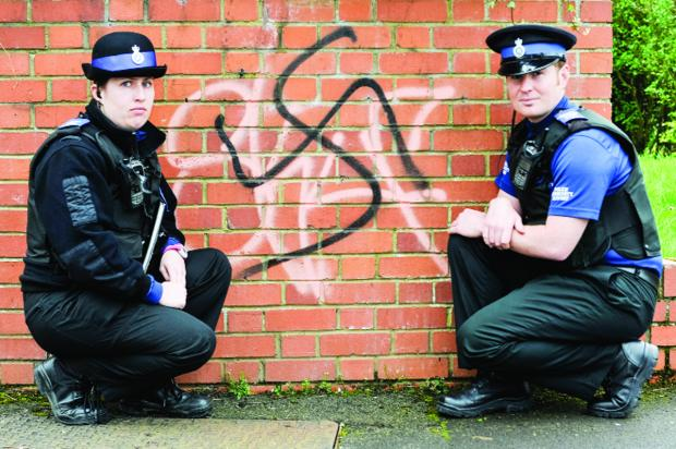 This Is Wiltshire: PCSOs Emma Turner and Rob Dentry with the graffiti on a wall in Walcot
