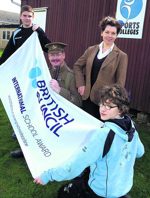 This Is Wiltshire: David Allton and arts leader Racheal Makepeace with Tim and Ryan with the flag marking the award         (PM1158) By PAUL MORRIS