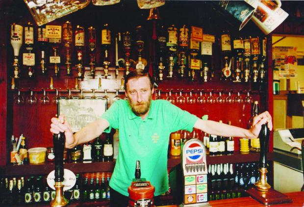 This Is Wiltshire: Noel Reilly in his natural habitat, behind the bar at The Beehive in Prospect Hill where his idiosyncratic nature came to the fore. He banned punters for being boring or having the wrong hair