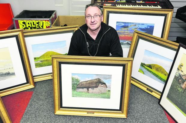 This Is Wiltshire: Alan Holmes with some of the paintings donated to the Goldenhar family support group to be sold