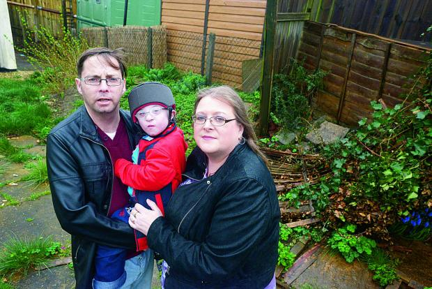 This Is Wiltshire: Disabled youngster Morgan Gibbons, centre, with dad Mark Willis and mum Ellen Gibbons in their back garden, which they need to convert into a safe space