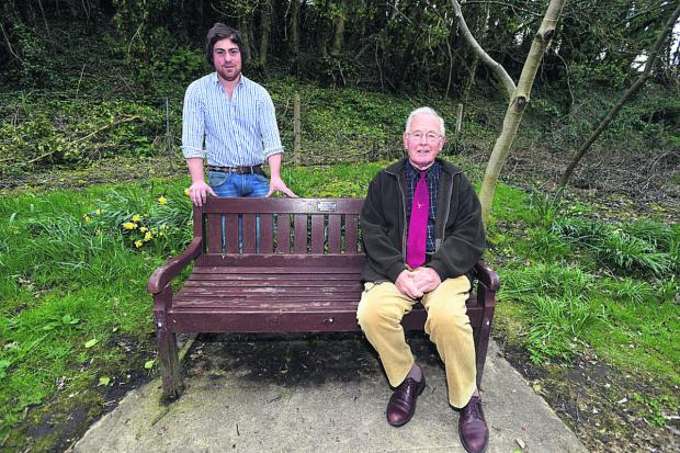 This Is Wiltshire: Ollie Simons, left, with Michael Way on the memorial bench to his wife Delia