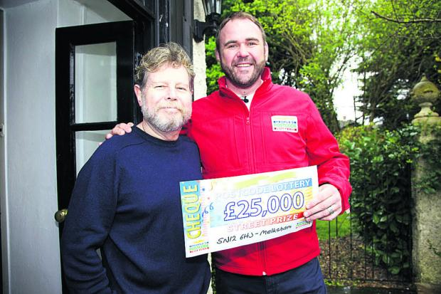 This Is Wiltshire: Richard Stephenson, left, receives his Postcode Lottery prize from former Welsh international rugby star Scott Quinnell