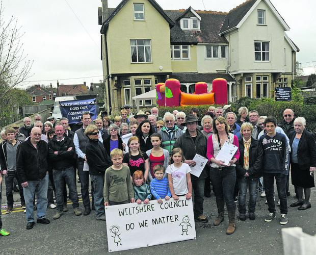 This Is Wiltshire: Angry residents assemble outside Greenwood House, right, to protest at Maplyn's plans