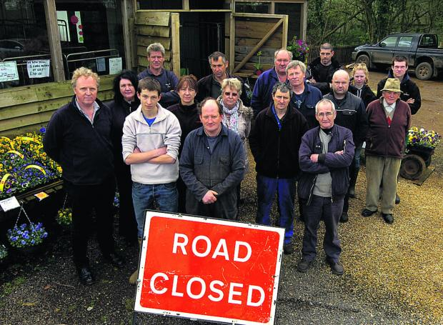 This Is Wiltshire: Lyneham Farm Shop owner Tim Webb, front centre, with business people and residents unhappy with road closures caused by the shutting of Dauntsey Lock railway bridge