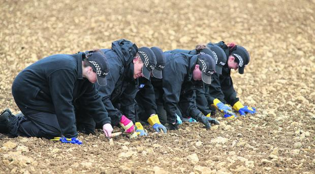 This Is Wiltshire: Police officers combing the field at Eastleach on Saturday
