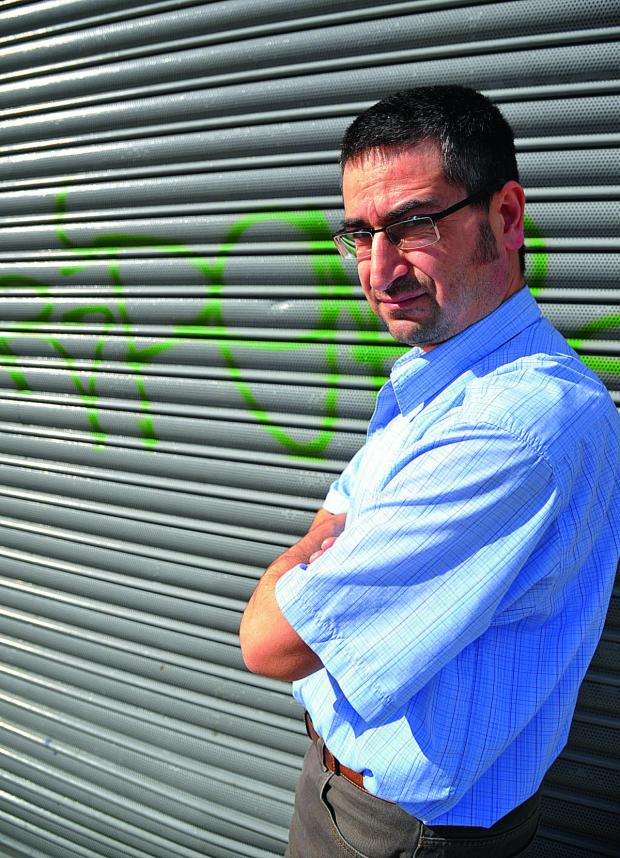 This Is Wiltshire: Husnu Cetin, manager of the Trident Fish bar in Victoria Road, is the latest victim of the spate of town centre graffiti as police appeal for residents to identify the tags